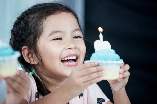 Cute asian child girl smiling and having fun to blow her birthday cupcake in party