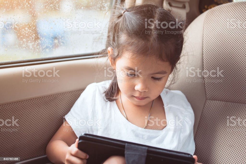 Cute asian child girl using smartphone, tablet in the car while raining stock photo