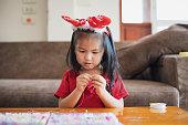 家の中で意図と楽しさと文字列にビーズをスレッドクリスマス衣装を身に着けているかわいいアジアの子供の女の子。