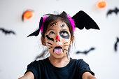 istock Cute asian child girl wearing halloween costumes and makeup having fun on Halloween celebration 1170811216