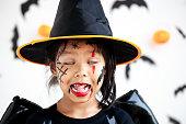 istock Cute asian child girl wearing halloween costumes and makeup having fun on Halloween celebration 1170811229