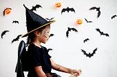 istock Cute asian child girl wearing halloween costumes and makeup having fun on Halloween celebration 1170811254