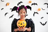 istock Cute asian child girl wearing halloween costumes and makeup having fun on Halloween celebration 1170811273