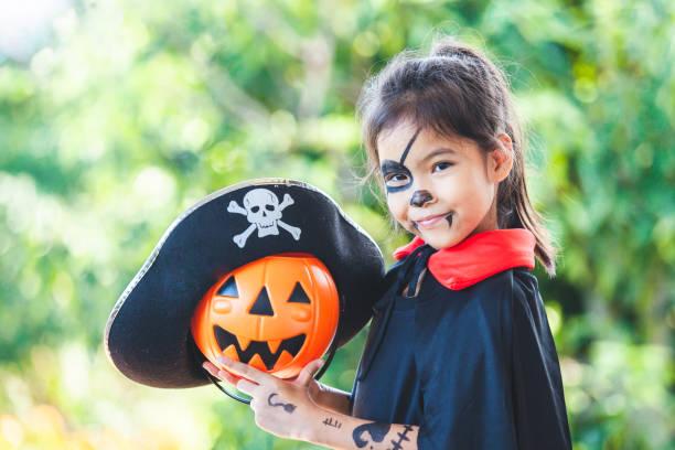 süße asiatische kind mädchen trägt halloween-kostüme und make-up spaß auf halloween-feier - piratenparty snacks stock-fotos und bilder