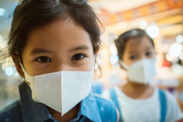 Niedliches asiatisches Mädchen trägt Schutzmaske gegen Luftsmog Verschmutzung mit PM 2.5 – Foto