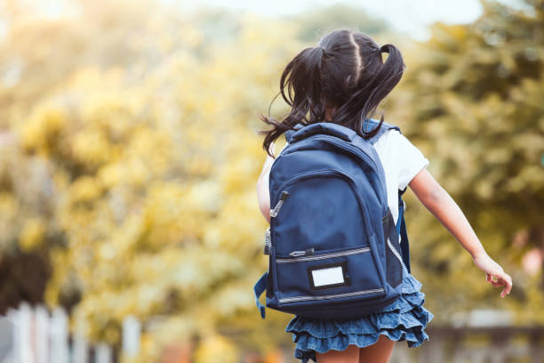 Cute asian child girl with backpack running and going to school stock photo