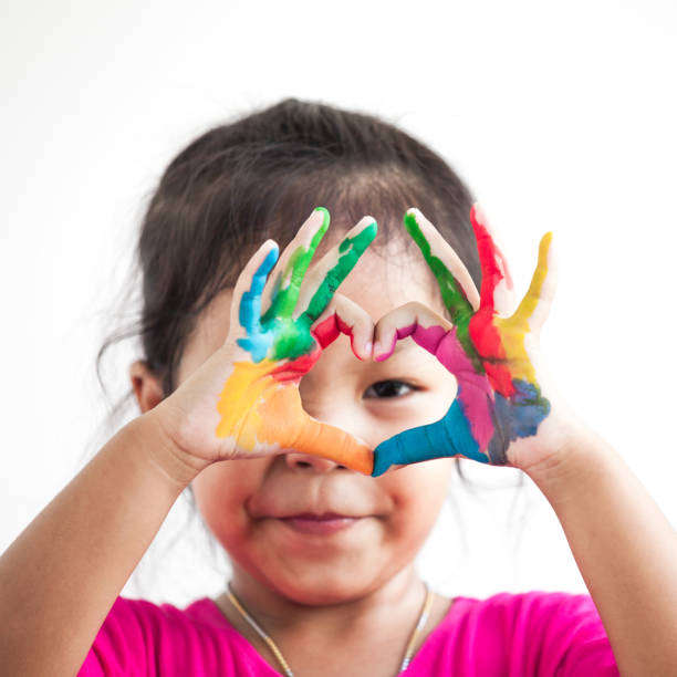 Cute asian child girl with hands painted make heart shape on white background - foto stock