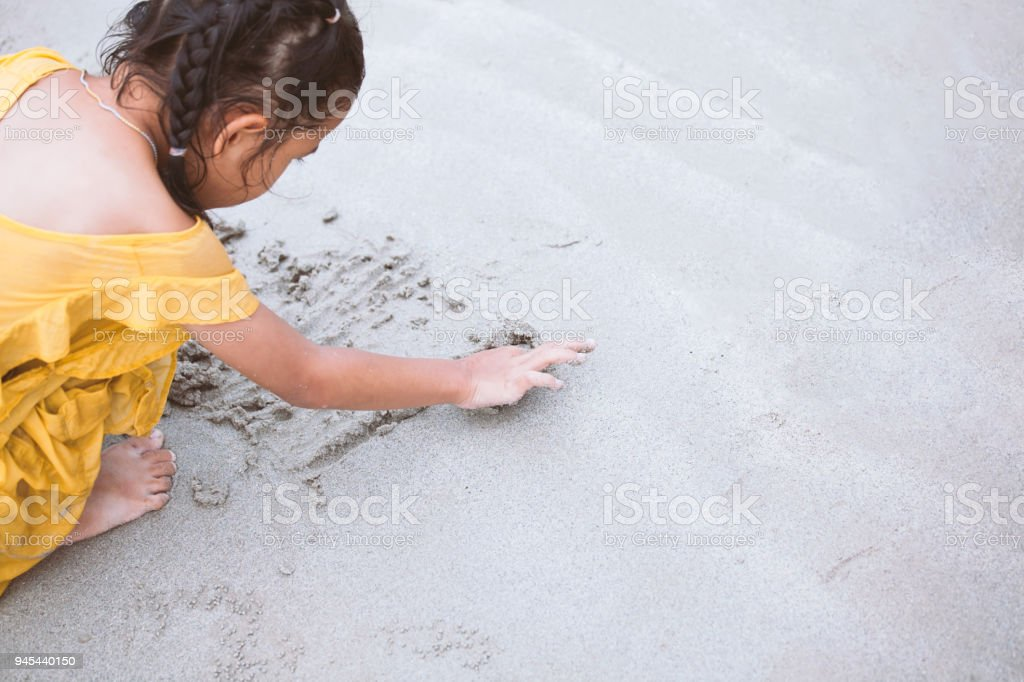Cute asian child girl writing in the sand and playing on the beach with fun stock photo