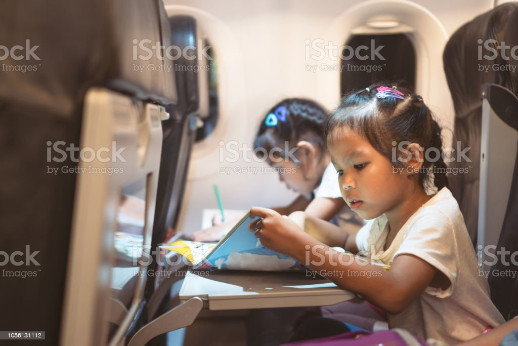 Cute Asian Child Girls Traveling By An Airplane And Spending