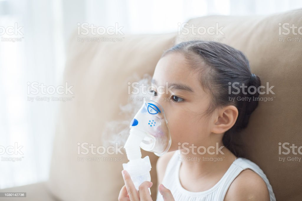 Cute Asian child patient inhalation therapy by the mask of inhaler...
