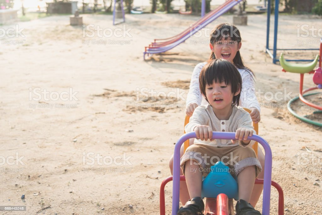 Cute asian child riding seesaw board at the playground stock photo