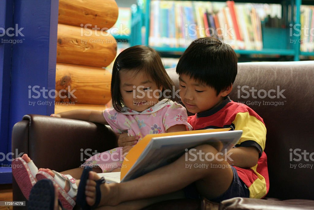 Cute Asian children reading a book together in preschool library royalty-free stock photo