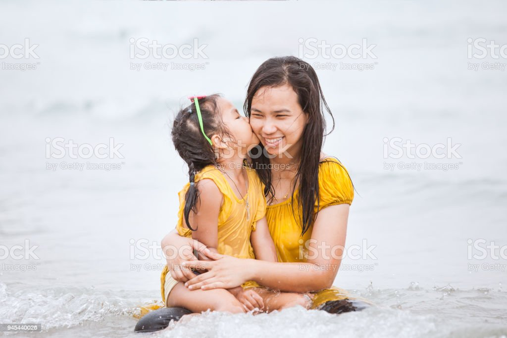 Cute asian daughter kiss her mother with love on beach in summer vacation stock photo