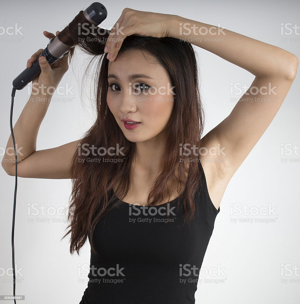 Cute Asian girl curling hair Cute Asian girl curling hair on white background Adult Stock Photo