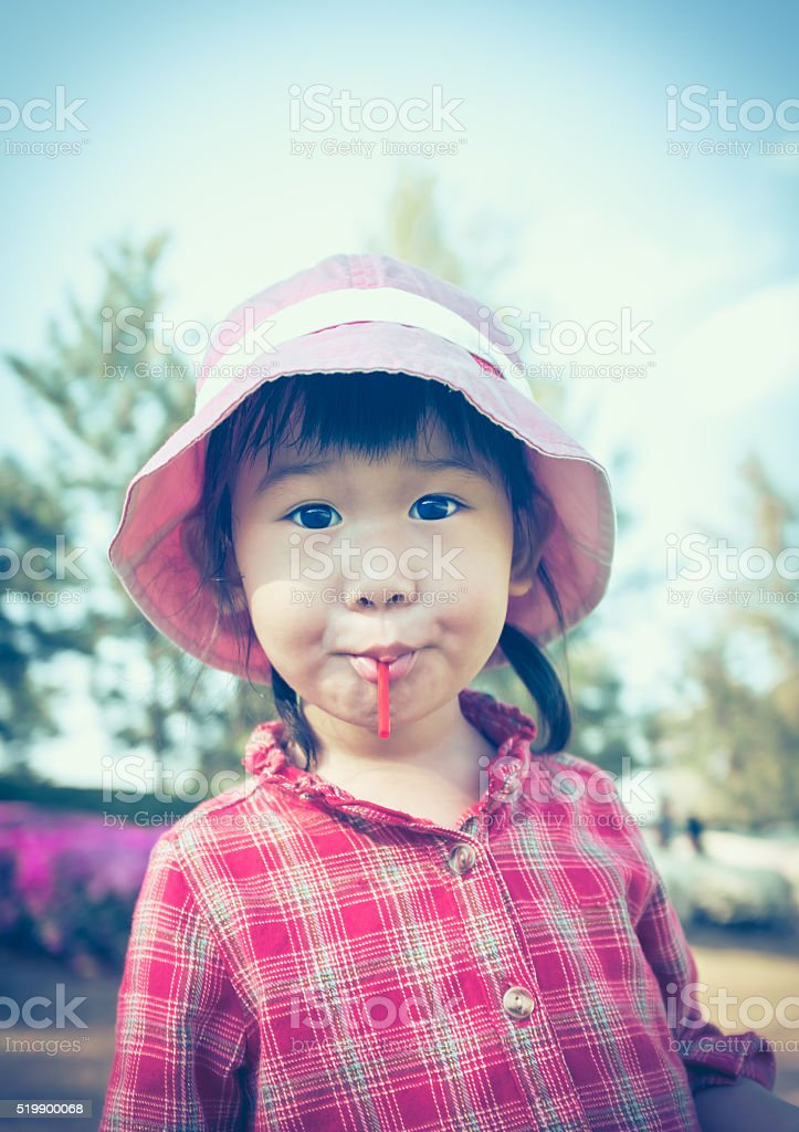 Cute asian girl eating a lollipop on nature background. stock photo