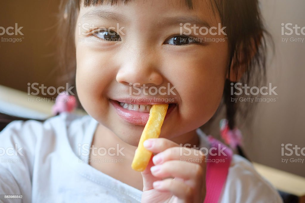 Cute Asian Girl Happy eating french fries. stock photo