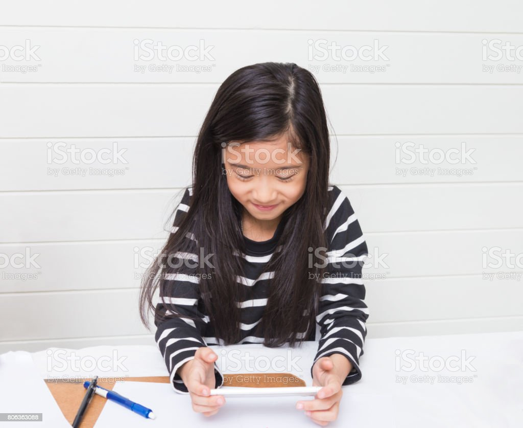 Cute asian girl kid happily watching video clip on the internet during her study time with smile on light background, selective focus stock photo