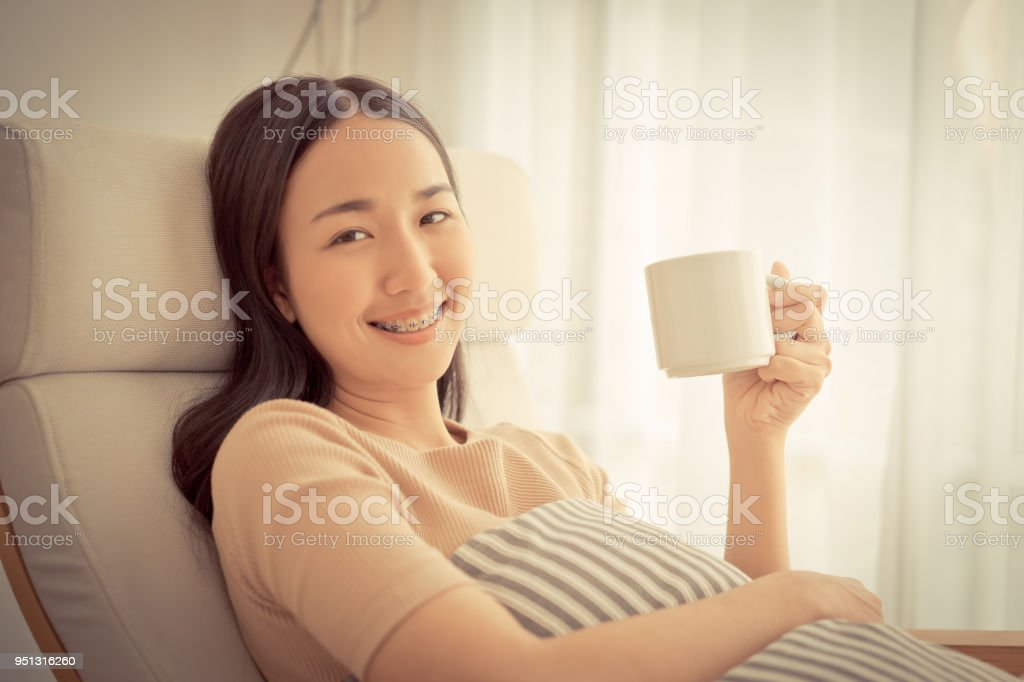 Cute Asian girl on sofa sitting and drinking coffee by the windows side view stock photo