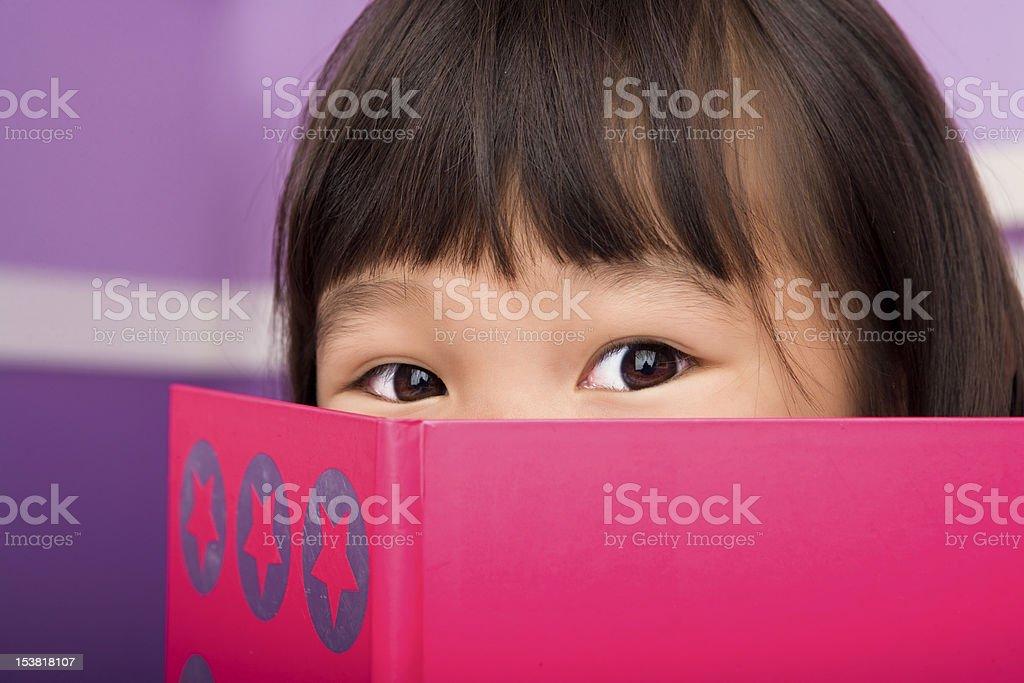 Cute asian girl reading in bedroom stock photo