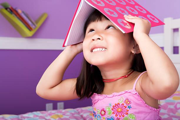 süße asiatische mädchen lesen im schlafzimmer - lila mädchen zimmer stock-fotos und bilder