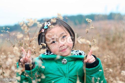 One cute Asian girl is showing victory signs via fingers in wild flower fields