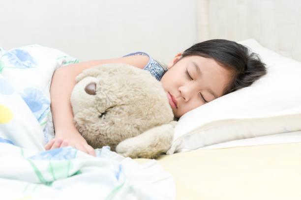 cute asian girl sleep and hug teddy bear on bed. stock photo