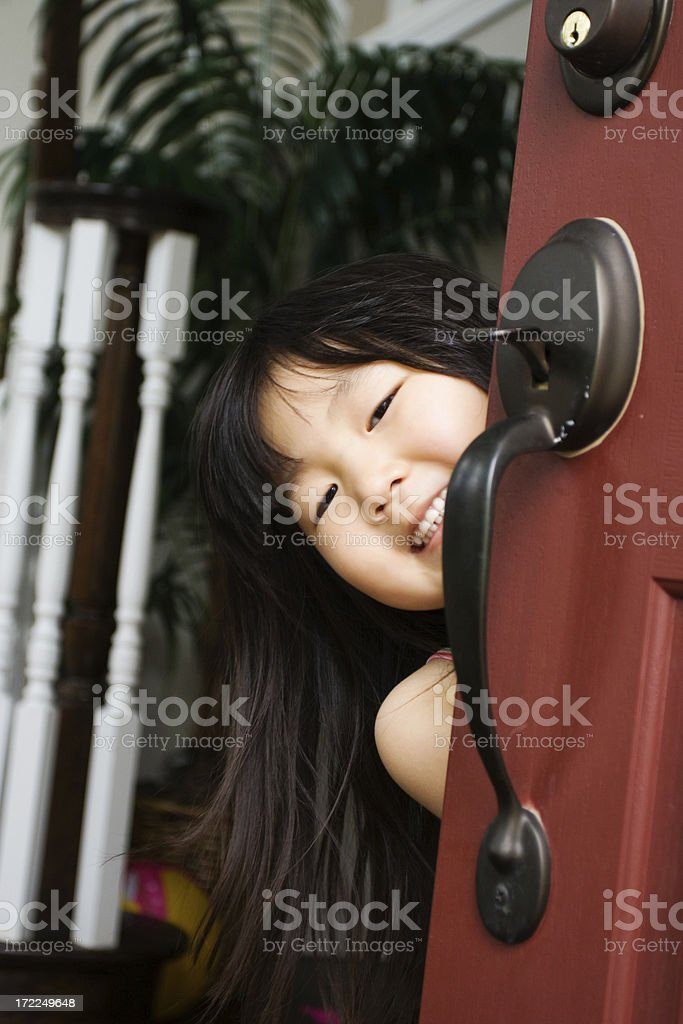 Cute Asian Girl Welcoming Behind Door royalty-free stock photo