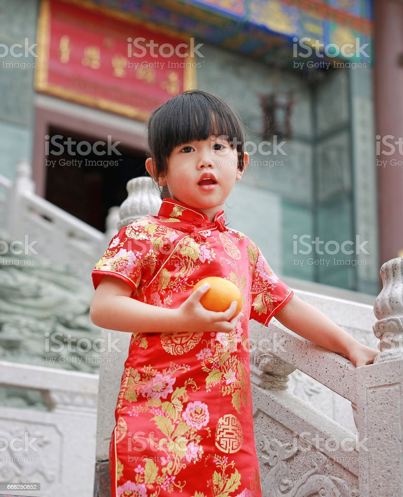 Cute asian kid girl in Traditional Chinese dress with holding sacred Orange. foto stock royalty-free