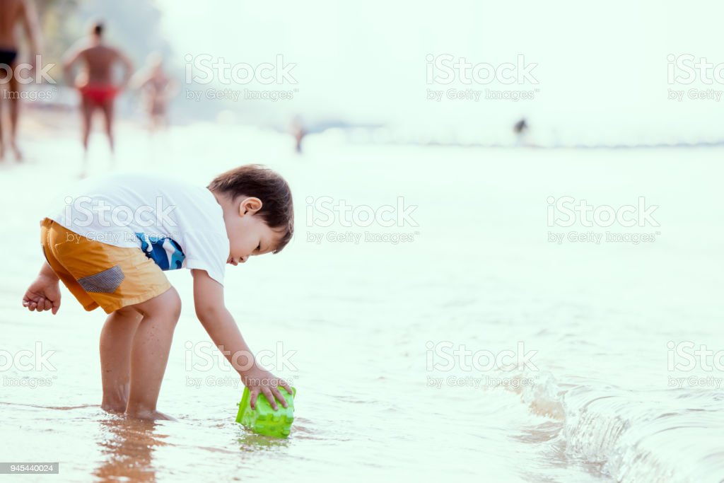 Cute asian little child boy having fun to play on beach in summer vacation stock photo