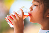 Cute asian little child girl drinking red juice water with ice from glass in the summer time