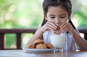 Cute asian little child girl eating cookie with milk for breakfast with happiness