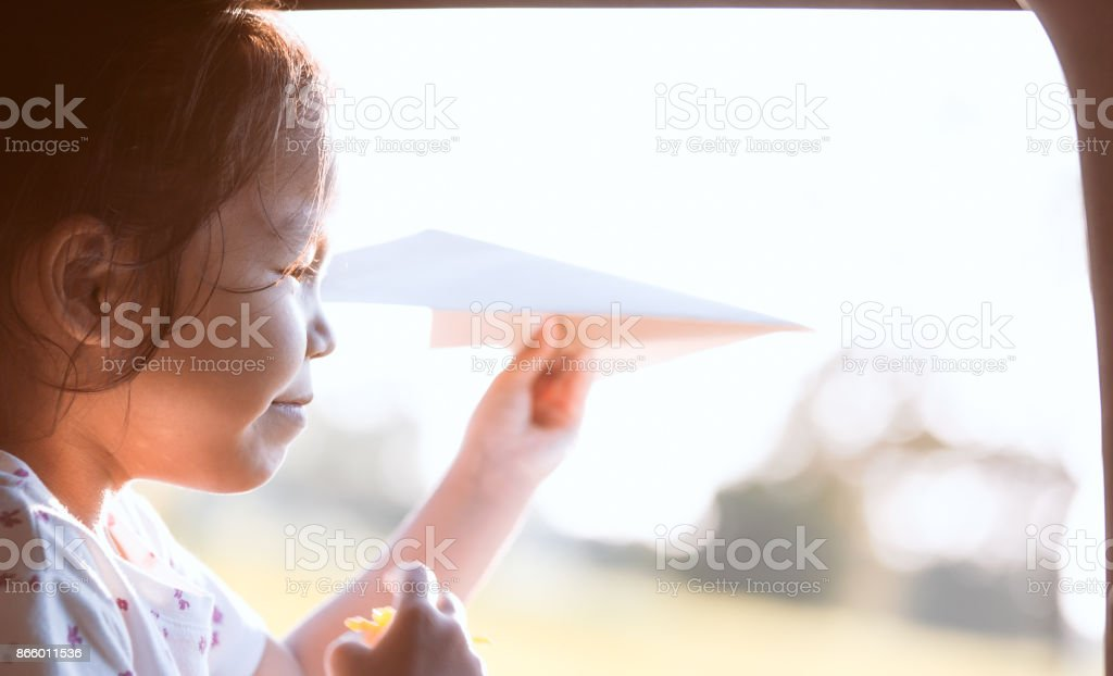 Cute asian little child girl having fun to play with toy paper airplane out of car window stock photo