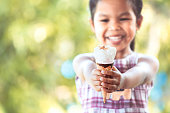 Cute asian little child girl holding delicious icecream cone in hand with fun and happiness