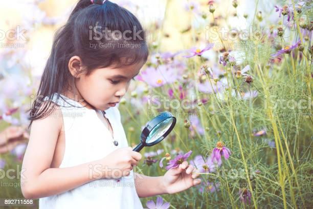 Cute asian little child girl looking beautiful flower through a in picture id892711558?b=1&k=6&m=892711558&s=612x612&h=rhwq lirx8yorgscg12pqu7wb8nbmtgmjhcte5jglsw=