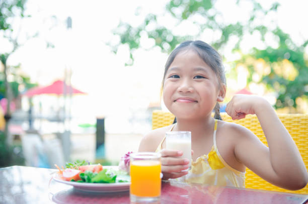 Cute asian little child girl making strong hand while drinking fresh milk stock photo
