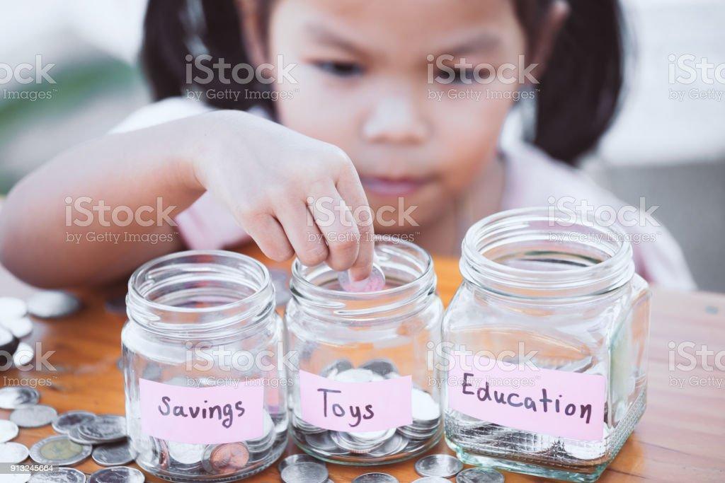 庭にガラス瓶の中にコインを入れて、アジアのかわいい小さな子女の子 ロイヤリティフリーストックフォト