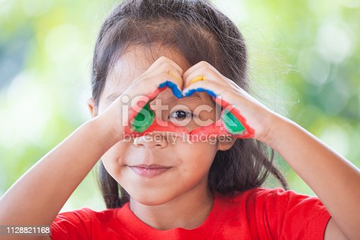 Cute asian little child girl with painted hands make heart shape colorful with fun and love