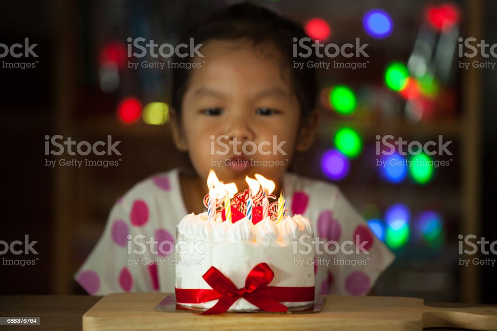 Cute asian little girl celebrating birthday and blowing candles on birthday cake stock photo