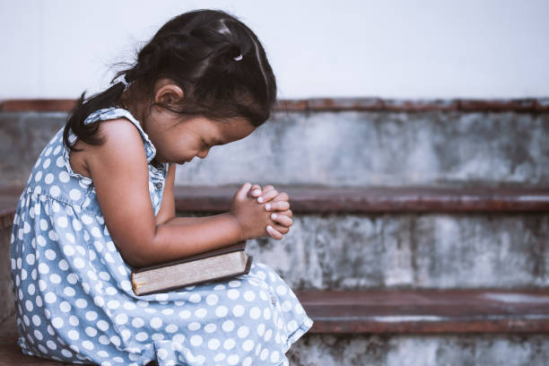 cute asian little girl closed her eyes and  folded her hand in prayer on a holy bible - religion stock pictures, royalty-free photos & images