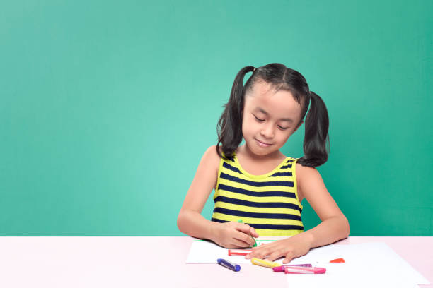Cute Asian Little Girl Drawing With Crayon While Sitting At
