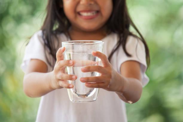 Niedliche kleine Asiatin hält Glas frisches Wasser in grüner Natur Hintergrund – Foto