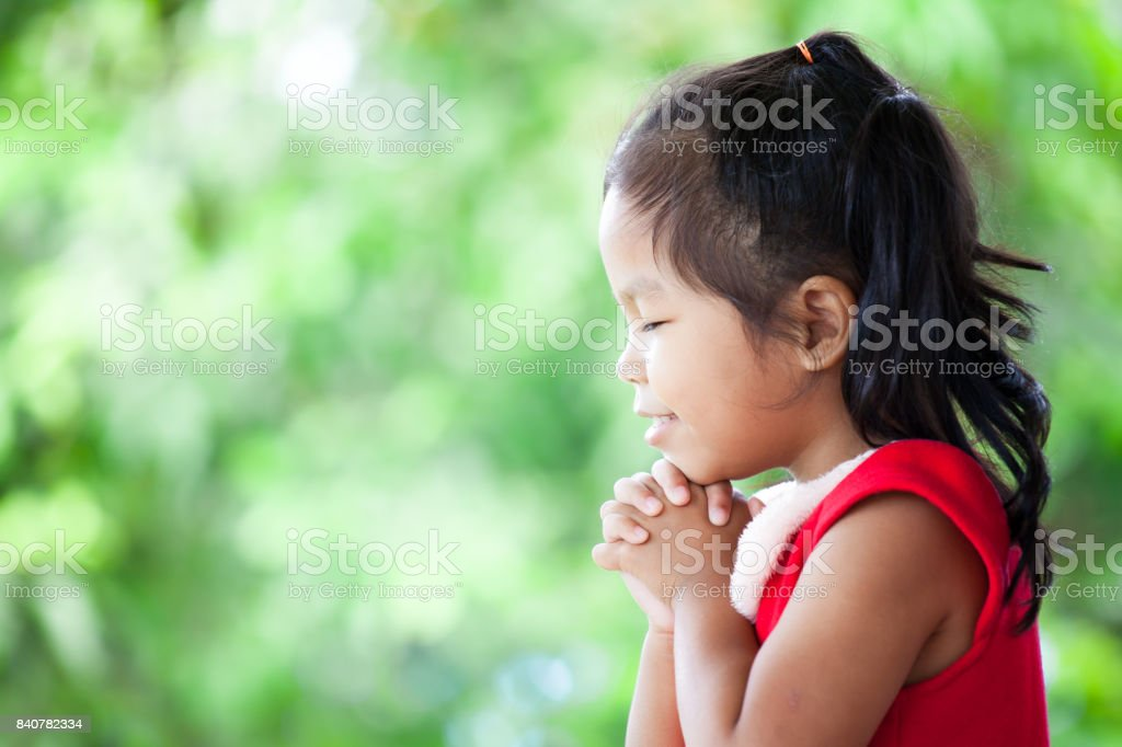 Cute asian little girl in christmas dress closed her eyes and folded her hand in prayer stock photo