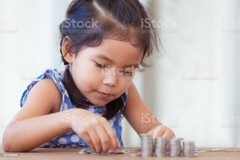 Cute asian little girl playing with coins making stacks of money stock photo