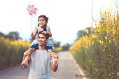 Cute asian little girl playing with wind turbine and riding on father's shoulders in the flower garden in vintage color tone. Father and daughter having fun to play together.