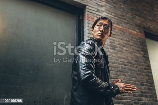 Attractive Asian man with long hair and leather jacket looking away