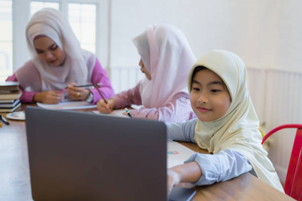 Cute asian muslim girls doing home work in classroom. stock photo