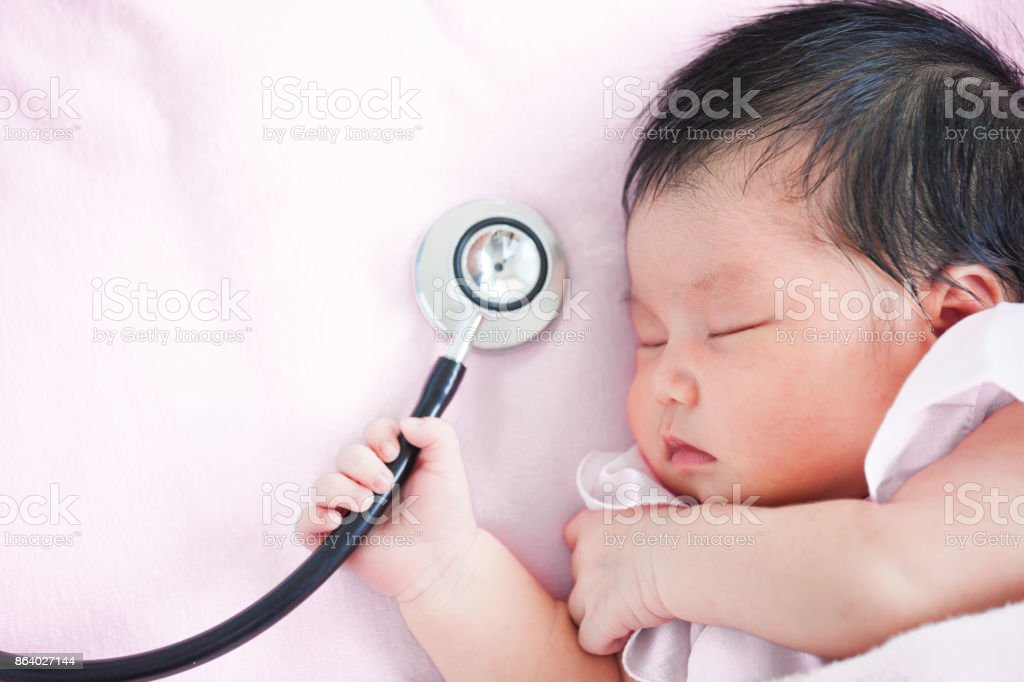 Cute asian newborn baby girl sleeping and holding medical stethoscope in hand stock photo
