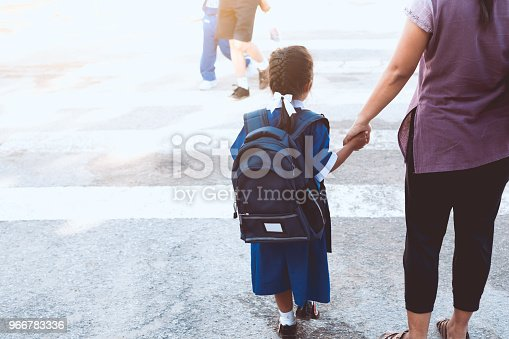 istock Cute asian pupil girl with backpack holding her mother hand and cross the road to go to school 966783336