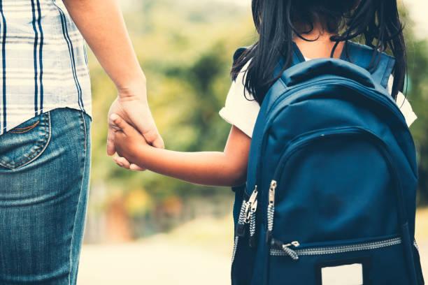 Süße asiatische Schüler Mädchen mit Rucksack ihre Mutter Hand haltend und zur Schule zu gehen – Foto