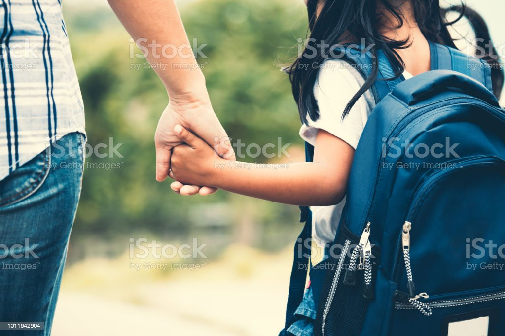 Cute asian pupil girl with backpack holding her mother hand and going to school royalty-free stock photo